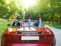 Lyckliga fria par som kör i röd retro bilcheerin Fotografering för Bildbyråer