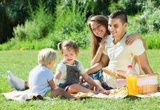 Lyckliga föräldrar med barn som har den utomhus- picknicken Royaltyfria Bilder