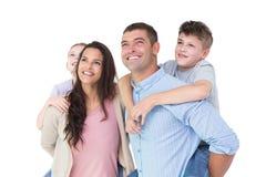Lyckliga föräldrar som på ryggen ger ritt till barn, medan se upp Royaltyfria Bilder