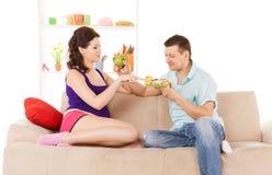 Lyckliga förväntande föräldrar hemma Fotografering för Bildbyråer