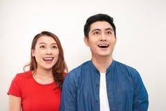Lyckliga fundersamma par se bort på vit bakgrund royaltyfri fotografi