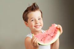 Lyckliga fyra år gammal pojke som ler med vattenmelon Arkivfoton