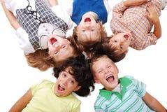 Lyckliga fyra barn tillsammans i cirkel Fotografering för Bildbyråer