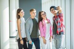 Lyckliga fyra vänner som tar självståenden till och med den smarta telefonen i högskola arkivbilder
