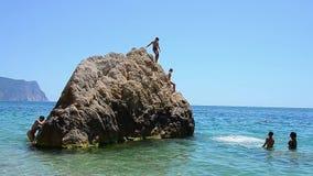 Lyckliga galna tokiga modiga barn hoppar farligt från en stor höjd med en enorm sten, korall i det azura vattnet, havet, havet lager videofilmer