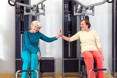 Lyckliga gamla kvinnor på idrottshallen som förbi trycker på, gömma i handflatan arkivfoto