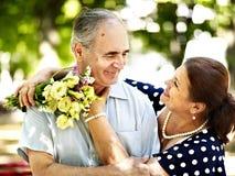 Lyckliga gamla par med blomman. Fotografering för Bildbyråer