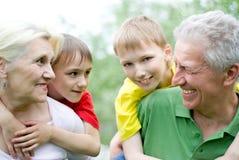 Lyckliga gammalare par med barnbarn Royaltyfri Fotografi