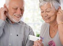 Lyckliga gammalare par med spelare mp3 Fotografering för Bildbyråer