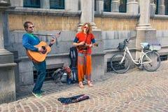 Lyckliga gatamusiker som utför för övergående byers Arkivbilder