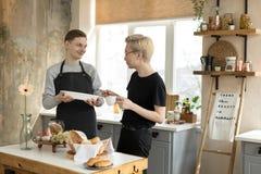 Lyckliga glade par, en asiat med blont hår i europé för exponeringsglas andra i tillfälliga kläder som har frukosten i köke royaltyfri foto