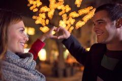 Lyckliga glade par med hjärta undertecknar danande vid deras händer Fotografering för Bildbyråer