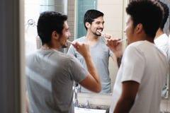 Lyckliga glade par som borstar tänder i badrum arkivfoto