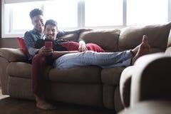 Lyckliga glade par som ser bilder på mobiltelefonen royaltyfria foton