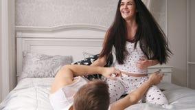 Lyckliga gladlynta älska par som har en kamp i säng, flicka som killar grabben arkivfilmer
