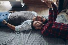 Lyckliga gladlynta caucasian glade par som bär tillfällig kläder som gör selfie på säng royaltyfri fotografi
