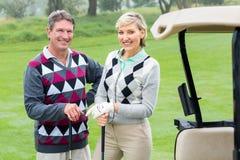 Lyckliga golfspelpar med golfbarnvagnen beside Arkivfoto