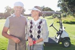 Lyckliga golfspelpar med golfbarnvagnen bakom Arkivbilder