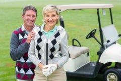 Lyckliga golfspelpar med golfbarnvagnen bakom Arkivfoton