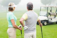 Lyckliga golfspelpar med golfbarnvagnen bakom Arkivfoto