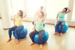 Lyckliga gravida kvinnor som övar på fitball i idrottshall Royaltyfri Fotografi