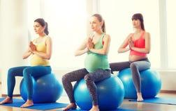 Lyckliga gravida kvinnor som övar på fitball i idrottshall Royaltyfri Foto