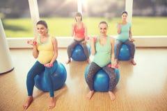 Lyckliga gravida kvinnor som övar på fitball i idrottshall Royaltyfri Bild