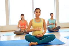 Lyckliga gravida kvinnor som övar på idrottshallyoga royaltyfri fotografi
