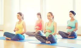 Lyckliga gravida kvinnor som övar yoga i idrottshall Royaltyfria Bilder