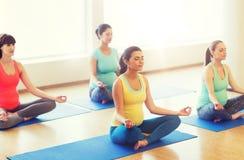 Lyckliga gravida kvinnor som övar yoga i idrottshall Fotografering för Bildbyråer