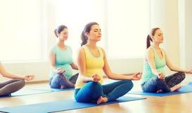 Lyckliga gravida kvinnor som övar yoga i idrottshall Royaltyfri Fotografi