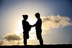 Lyckliga gravida par på solnedgångstranden Arkivfoton