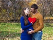 Lyckliga gravida par som kramar sig Fotografering för Bildbyråer