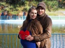 Lyckliga gravida par som kramar sig Royaltyfri Bild