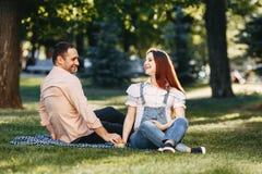 Lyckliga gravida par tycker om tid tillsammans fotografering för bildbyråer