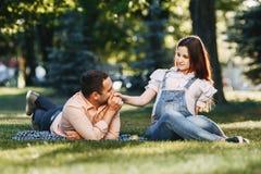 Lyckliga gravida par tycker om tid tillsammans arkivbilder