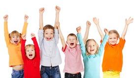 Lyckliga gruppbarn med deras händer upp Royaltyfri Bild