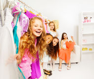 Lyckliga gulliga flickor i shoppa som väljer kläder Arkivbilder