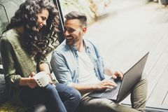 Lyckliga gulliga par som är förälskade med bärbara datorn som dricker kaffe arkivbild