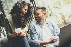 Lyckliga gulliga par som är förälskade med bärbara datorn som dricker kaffe och smili royaltyfri foto