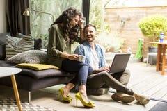 Lyckliga gulliga par som är förälskade med bärbara datorn som dricker kaffe och smili royaltyfri bild