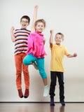 Lyckliga gulliga ungar liten flicka och hoppa för pojkar Arkivbilder