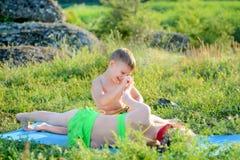 Lyckliga gulliga ungar som kelar på mattt på gräsen royaltyfri foto