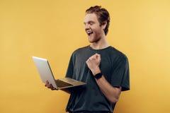 Lyckliga Guy Celebrating Success Using Laptop royaltyfri fotografi