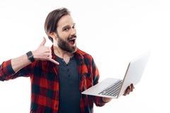 Lyckliga Guy Hold Laptop och visningen kallar mig gesten arkivfoto
