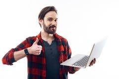 Lyckliga Guy Holding Light Laptop och showtummar upp royaltyfria foton