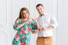 Lyckliga härliga gravida par förvänta tillsammans ett barn Man och kvinna i vita minimalistic inre visninghjärtor med händer Fotografering för Bildbyråer