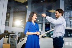 Lyckliga härliga kvinnahäleritangenter från en ny bil på den auto visningslokalen arkivbilder