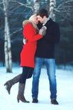 Lyckliga härliga par som kramar i vinterdag arkivbild