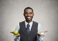 Lyckliga håll för affärsman gör grön äpplet och preventivpillerar Royaltyfria Bilder